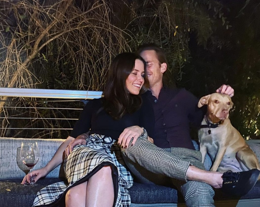 Sophia and Grant cozy up on a couch outside with a dog sitting nearby