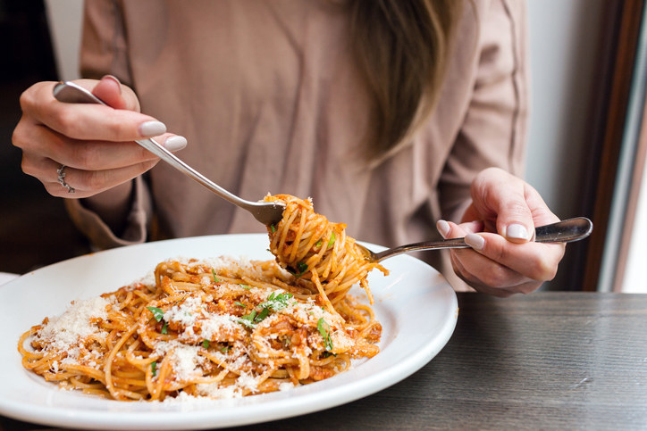 Woman putting pasta on her fork