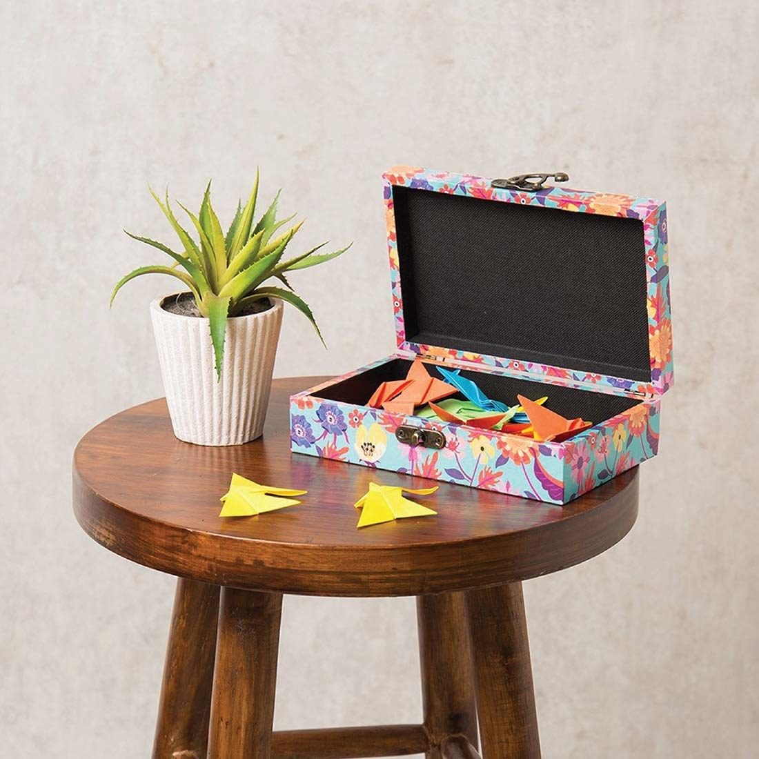 A floral box with colourful origami in it on a table next to a plant