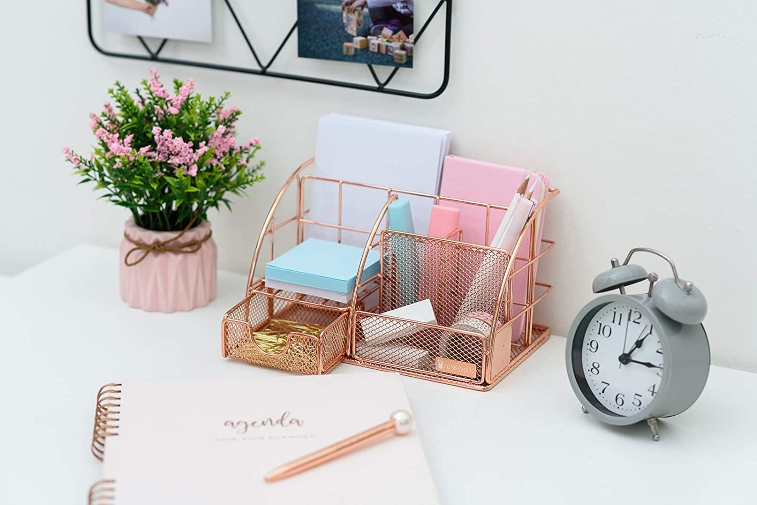 A rose gold organiser on a desk with stationery in it next to a clock and a flower pot