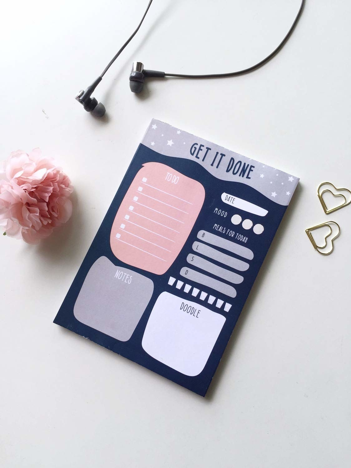 Sheets of the planner next to metal hearts and a rose