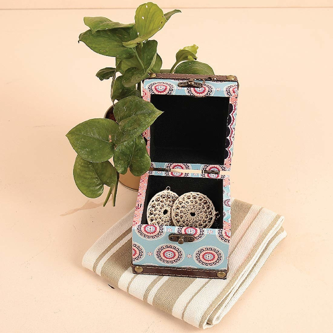 A trinket box with earrings on it next to a plant