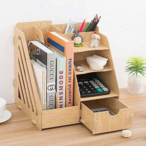 A desk organiser with books, calculator, tags and a watch in it