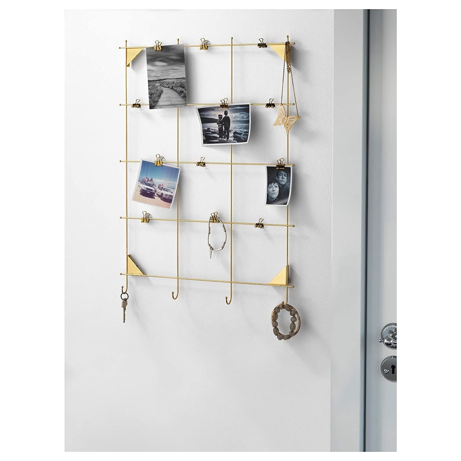 A brass wall grid with photographs, keys, and bracelets on it