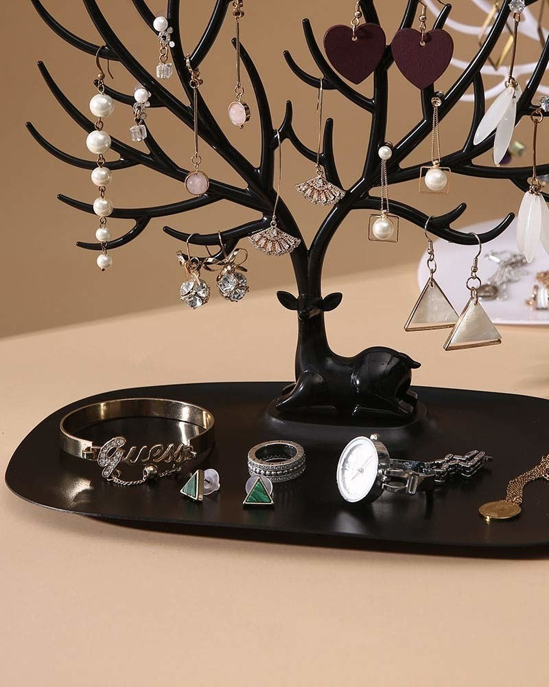 A black deer organiser with earrings and other jewellery items on it
