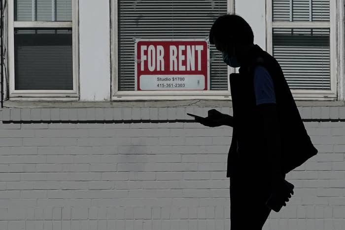 """A man walks in front of a """"for rent"""" sign in a window of a residential property"""