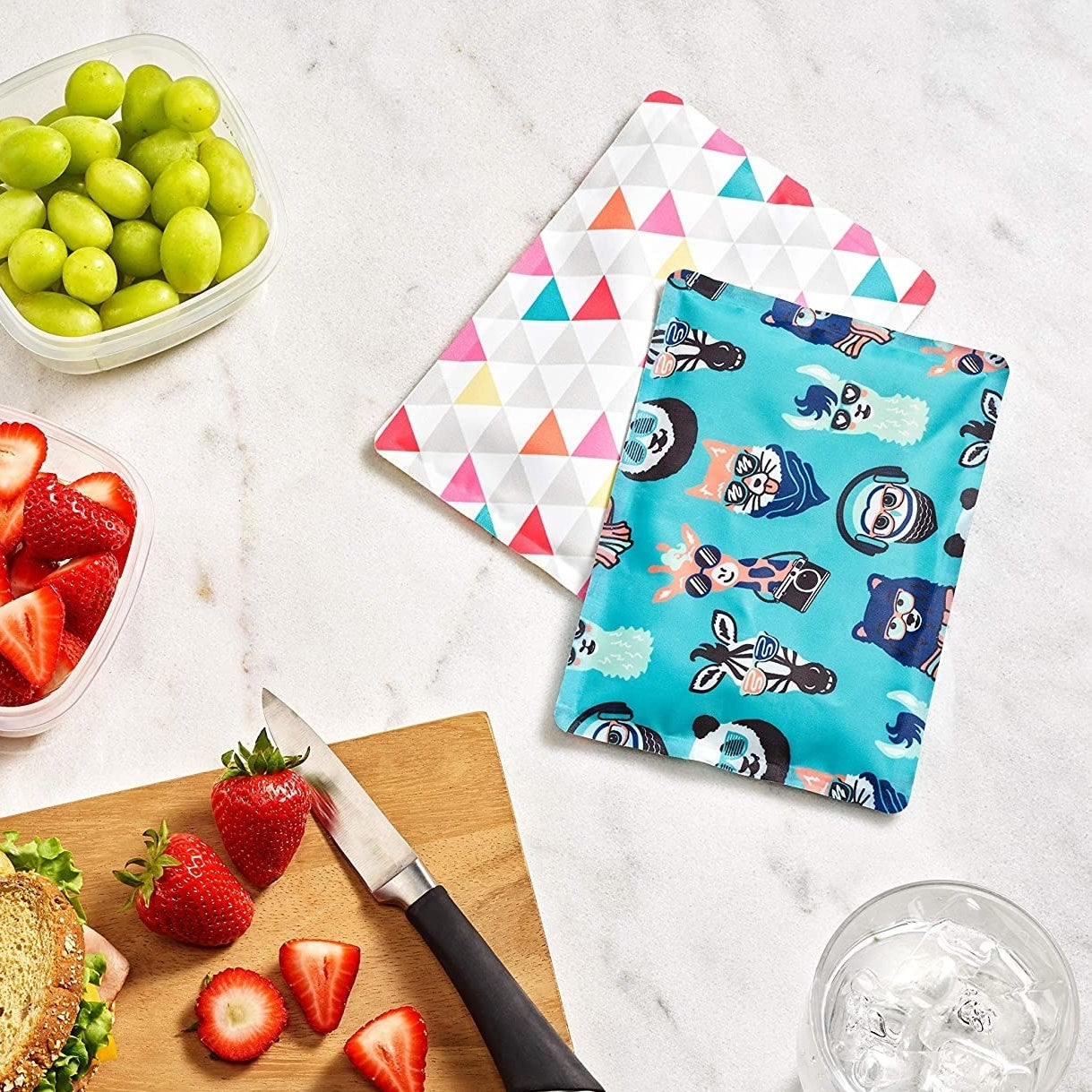 two vibrant ice packs on a table next to a cutting board and glass of water