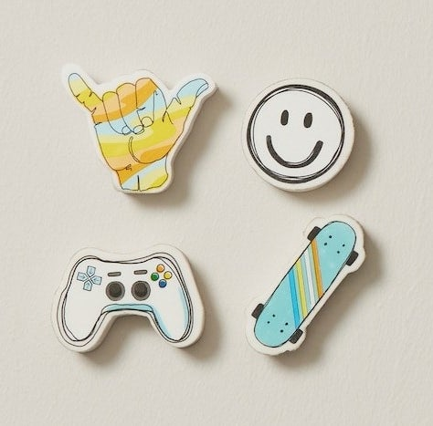 four erasers in various shapes, including a game controller, skate board, smiley face, and radical hand