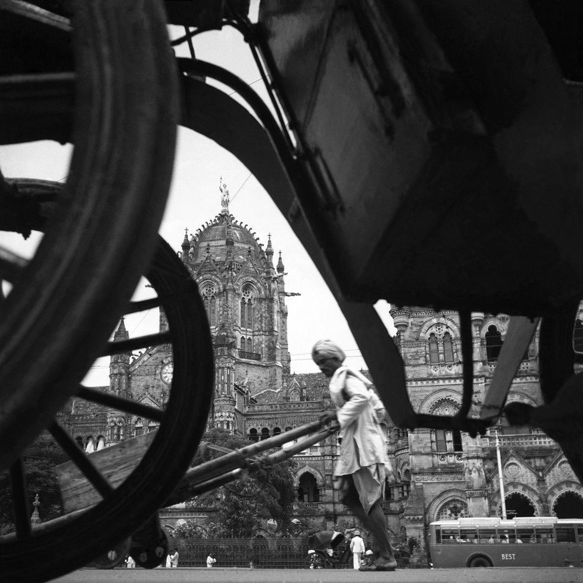 A man pushes a rickshaw in India, seen through the wheels of a cart with an ornate building in the background