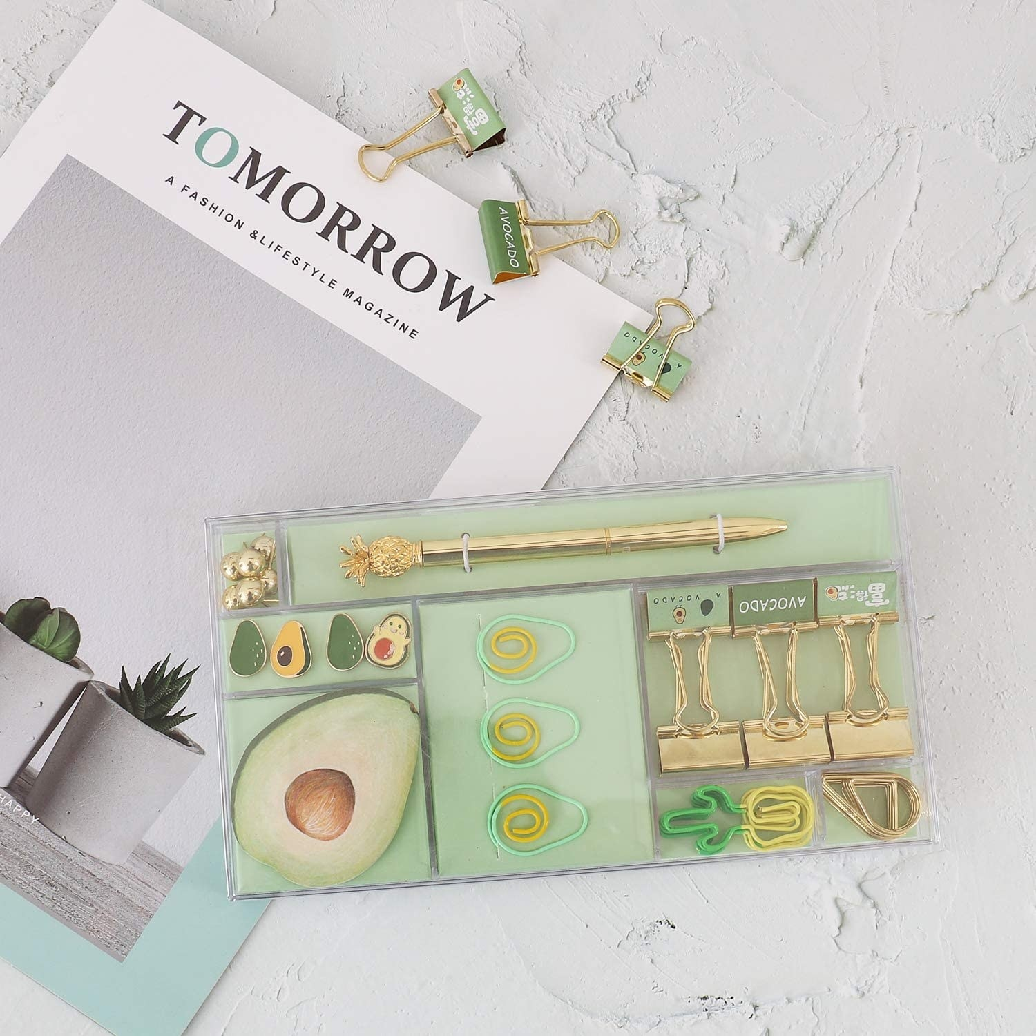 an avocado themed stationery set on a table next to a magazine