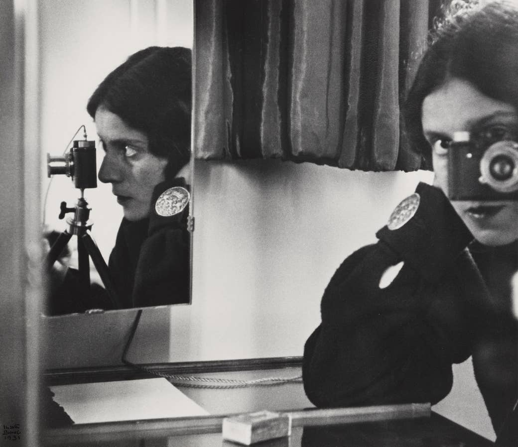 A woman looks through a camera lens while reflected by a mirror on her right