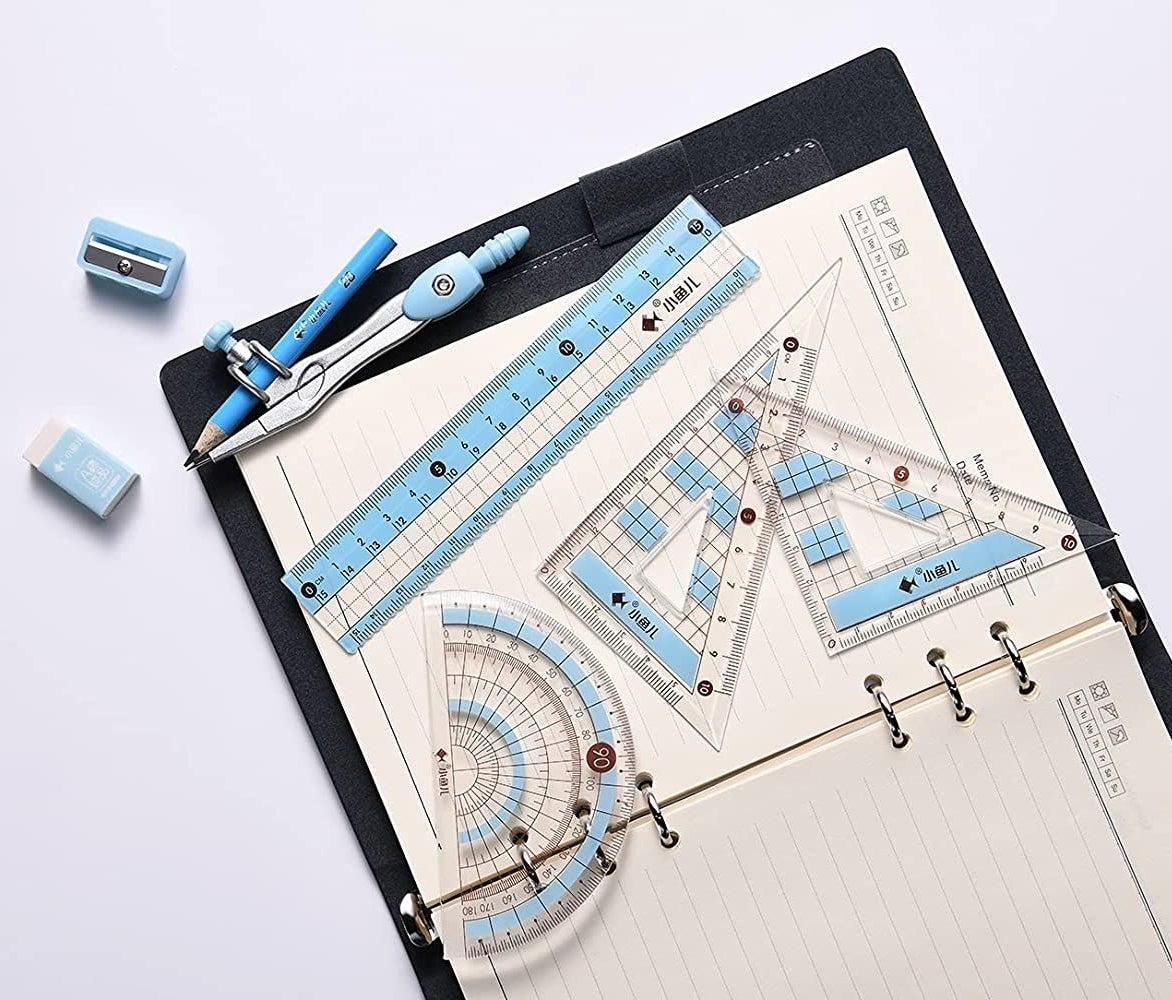 a compass, protractor, eraser, pencil, and three rulers on top of a binder