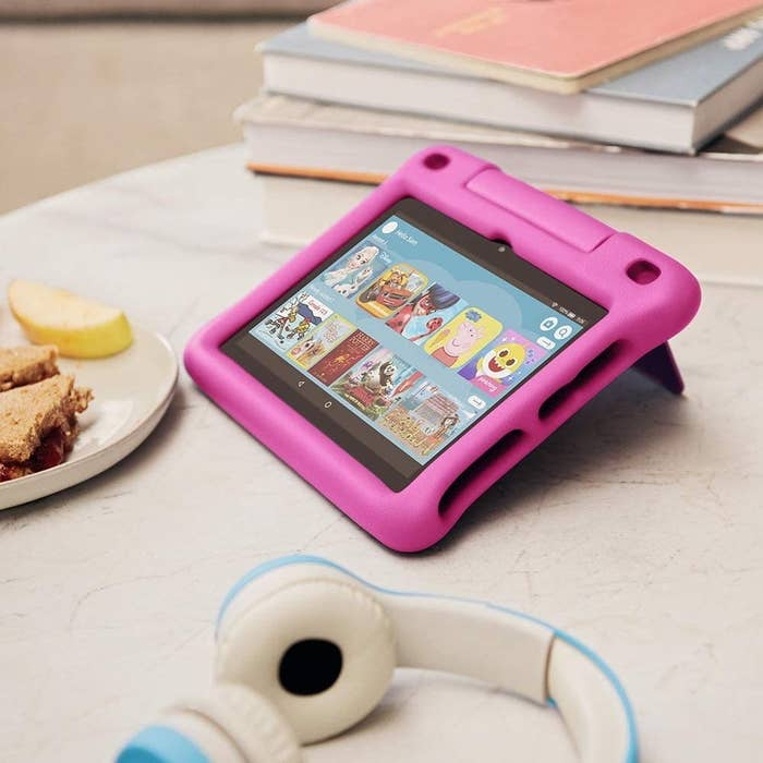 the tablet on a table next to a pair of head phones