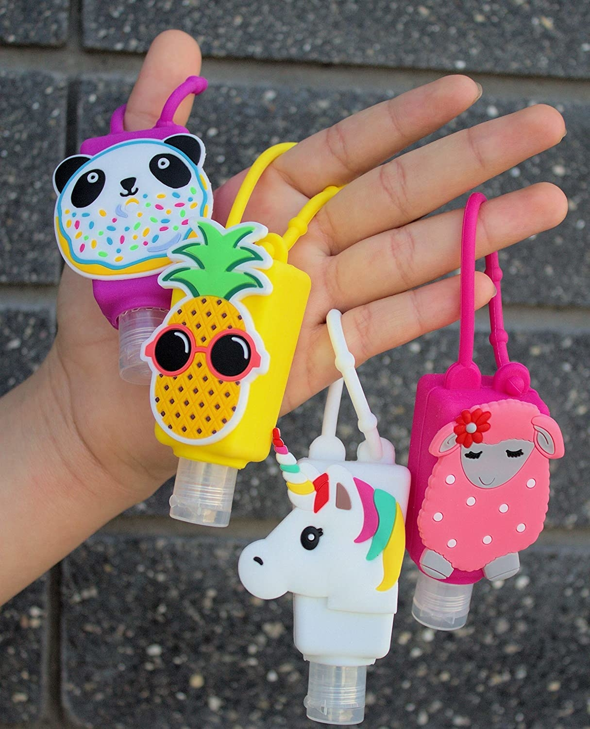 a person holding four cute sanitizer keychain bottles