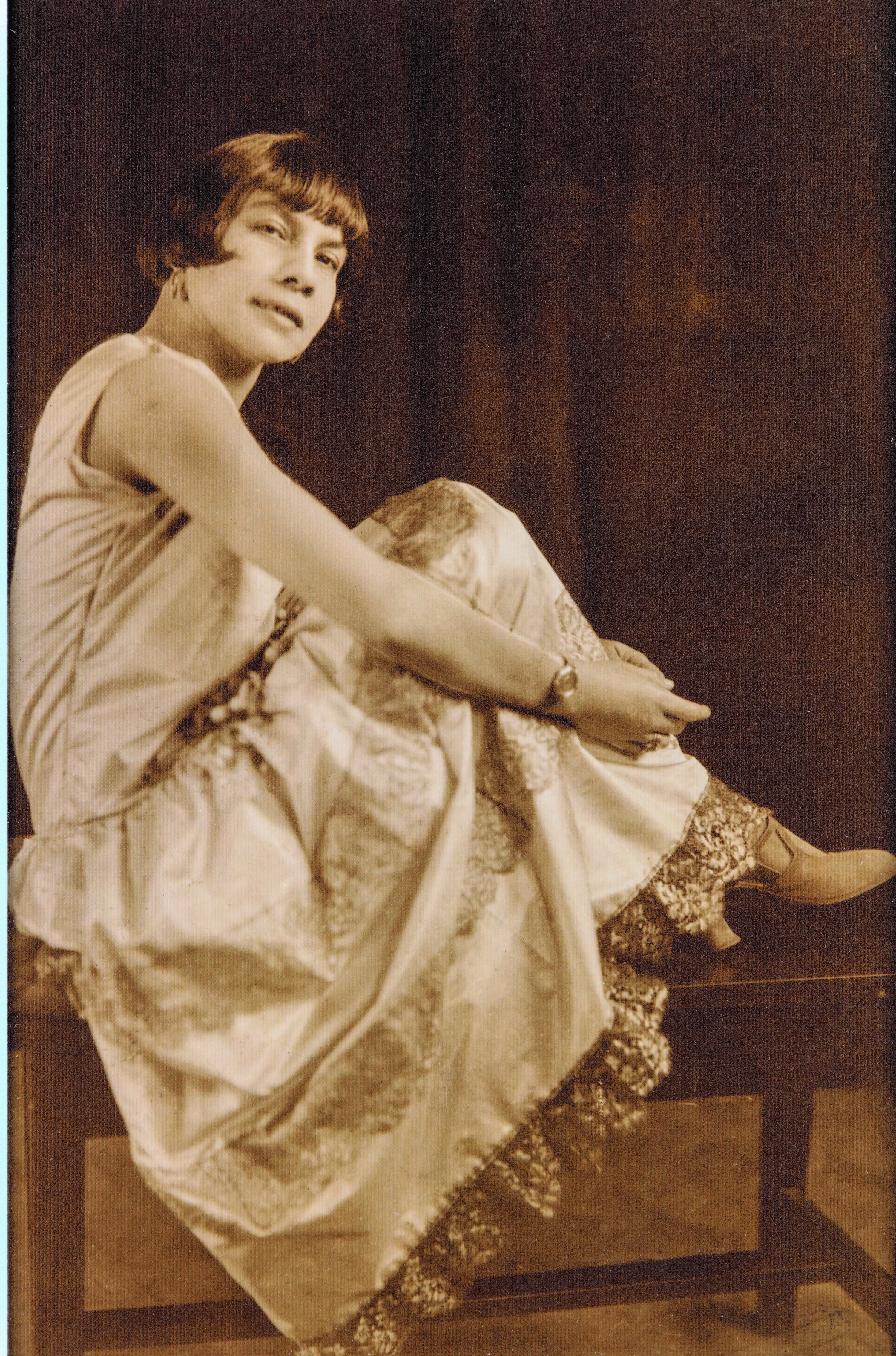 A woman in an evening dress sitting with her feet up on a bench, looking past the camera