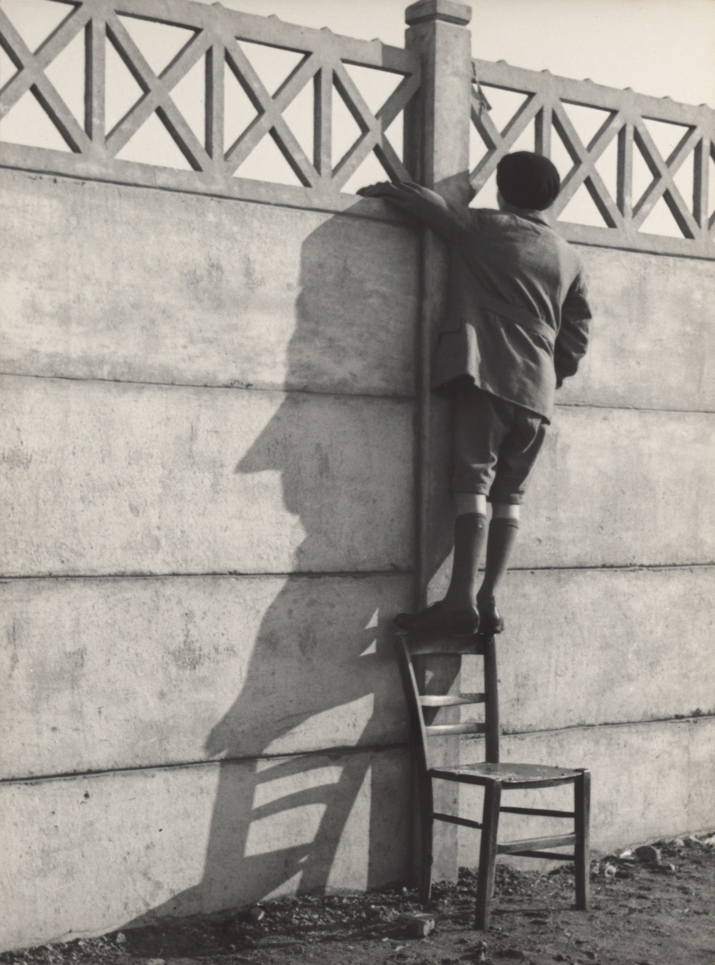 A boy stands on the back of a chair to get a vantage point over a large stone wall