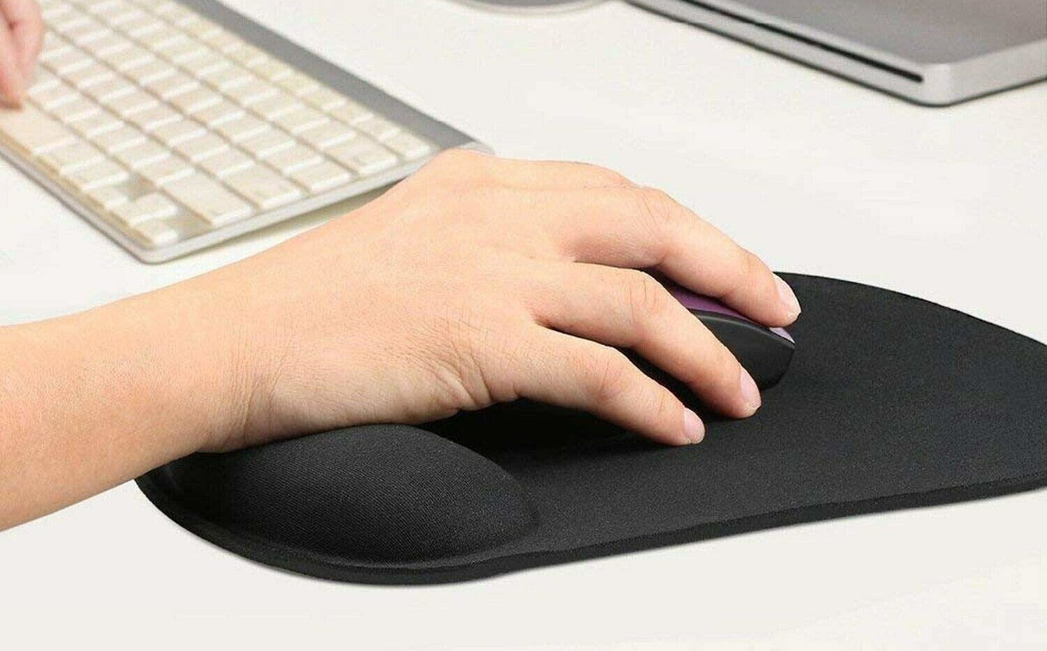 A person using a mouse on an ergonomic pad next to a keyboard