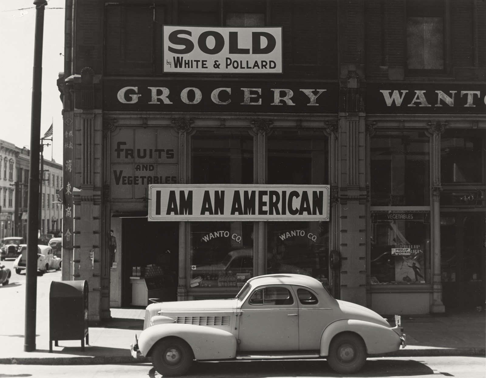 """A sign reads """"I Am an American"""" over a fruit and vegetable store with a car on the street outside"""