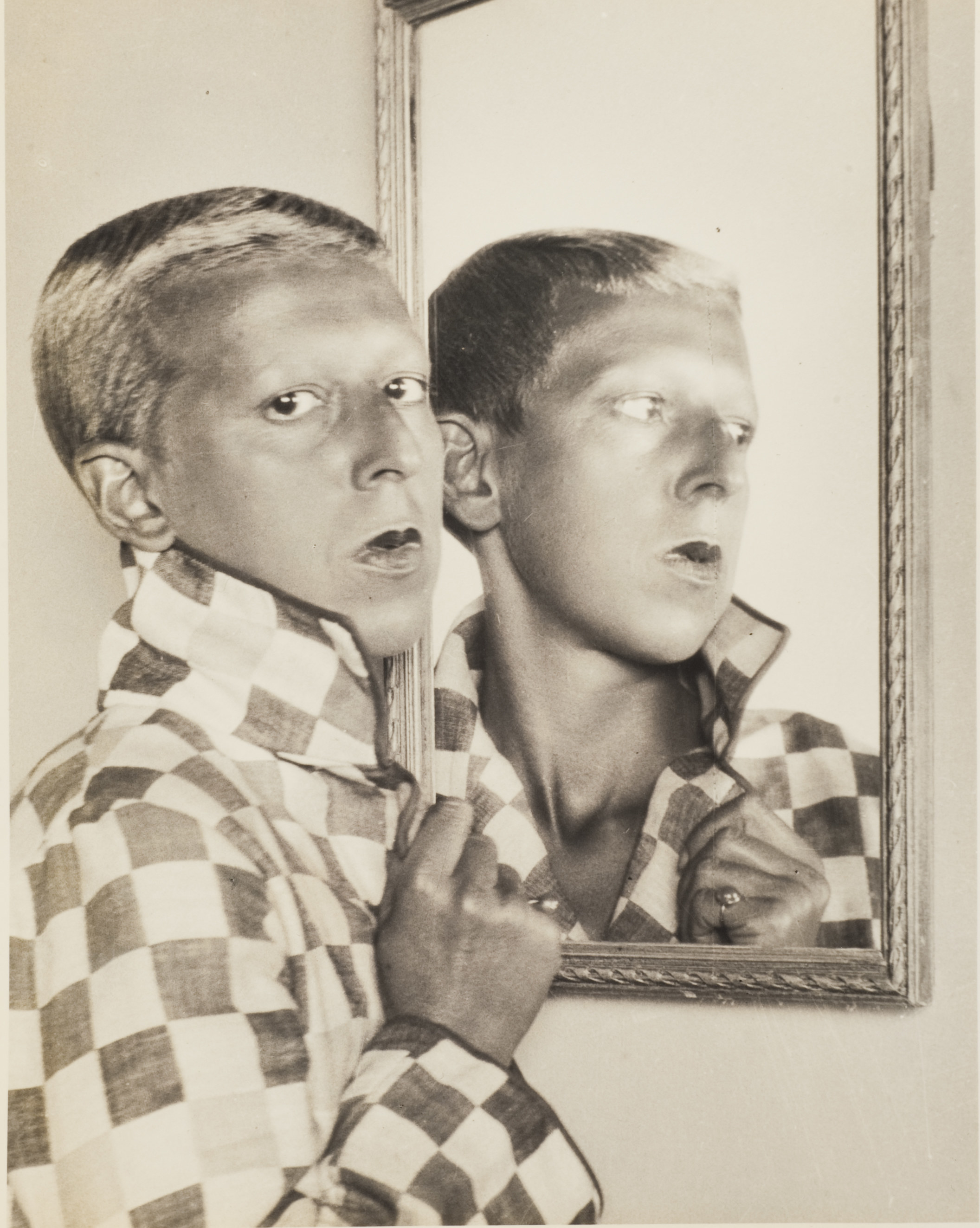 A person with short hair in a checkered jacket, looking back at the camera reflected in a mirror