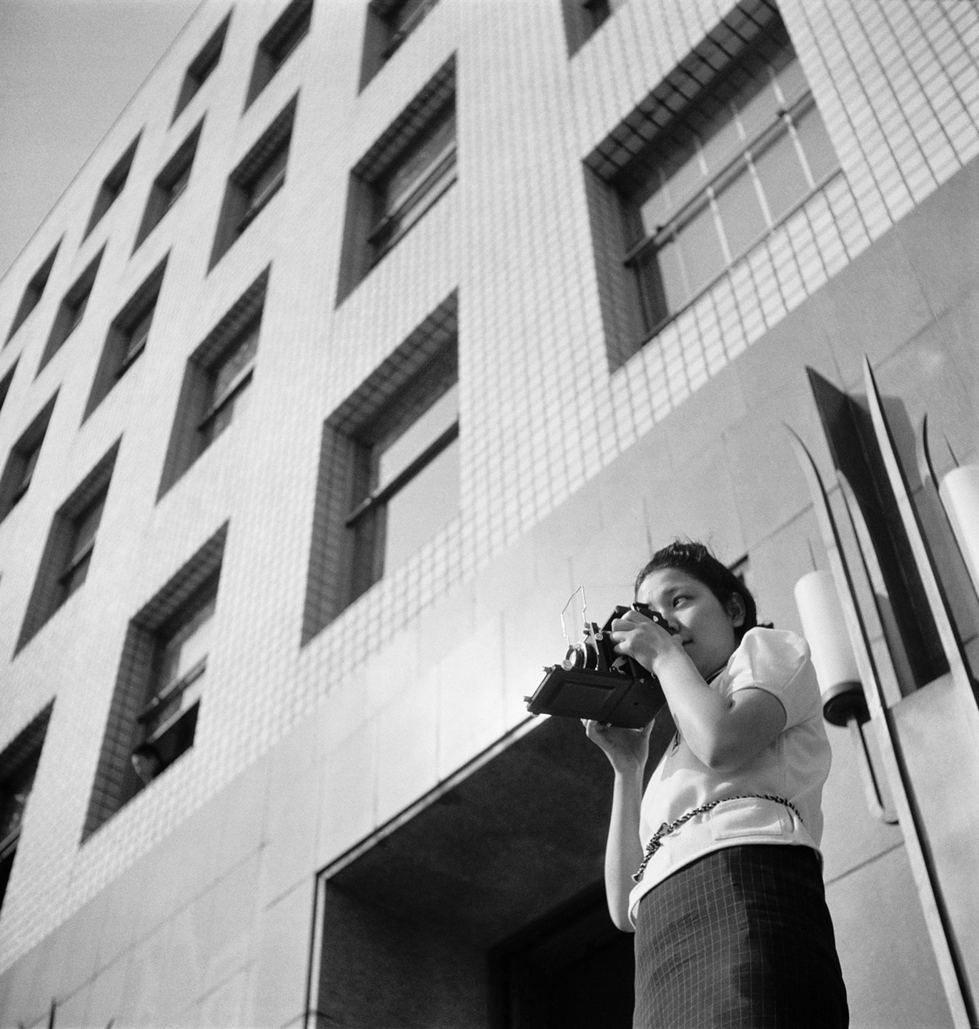 A woman aims a camera while she stands in front of a building