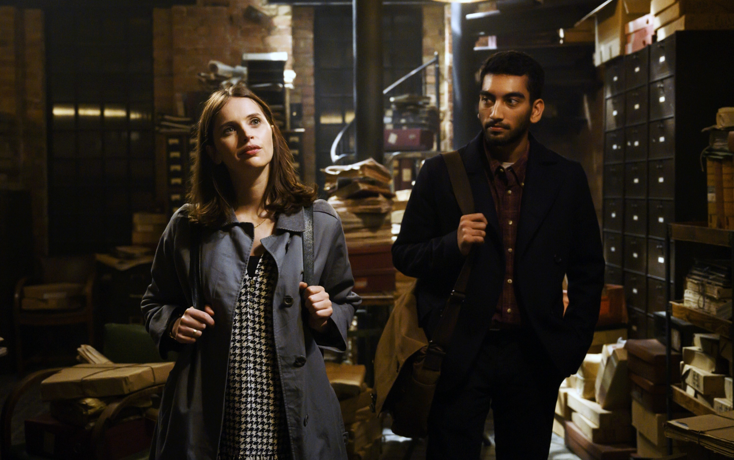 Ellie in dress and dark trench coat looking up at something, Rory stands behind her to the side looking at her, they are both in a cluttered archive room