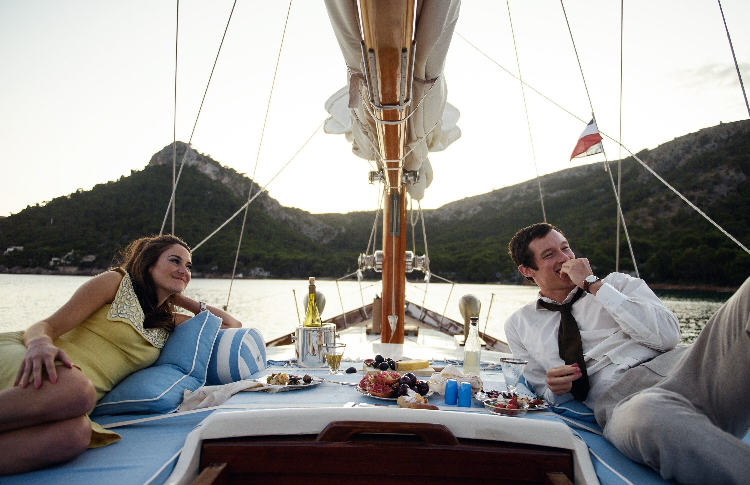Jennifer and Anthony lounging at the bow of a sailboat with berries and snacks and chilled champagne between them, on a body of water with tree-topped mountains behind them