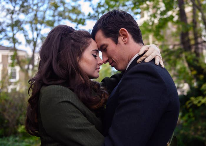 Sideview of Jennifer in an overcoat embracing Anthony in suit, faces touching, in a park