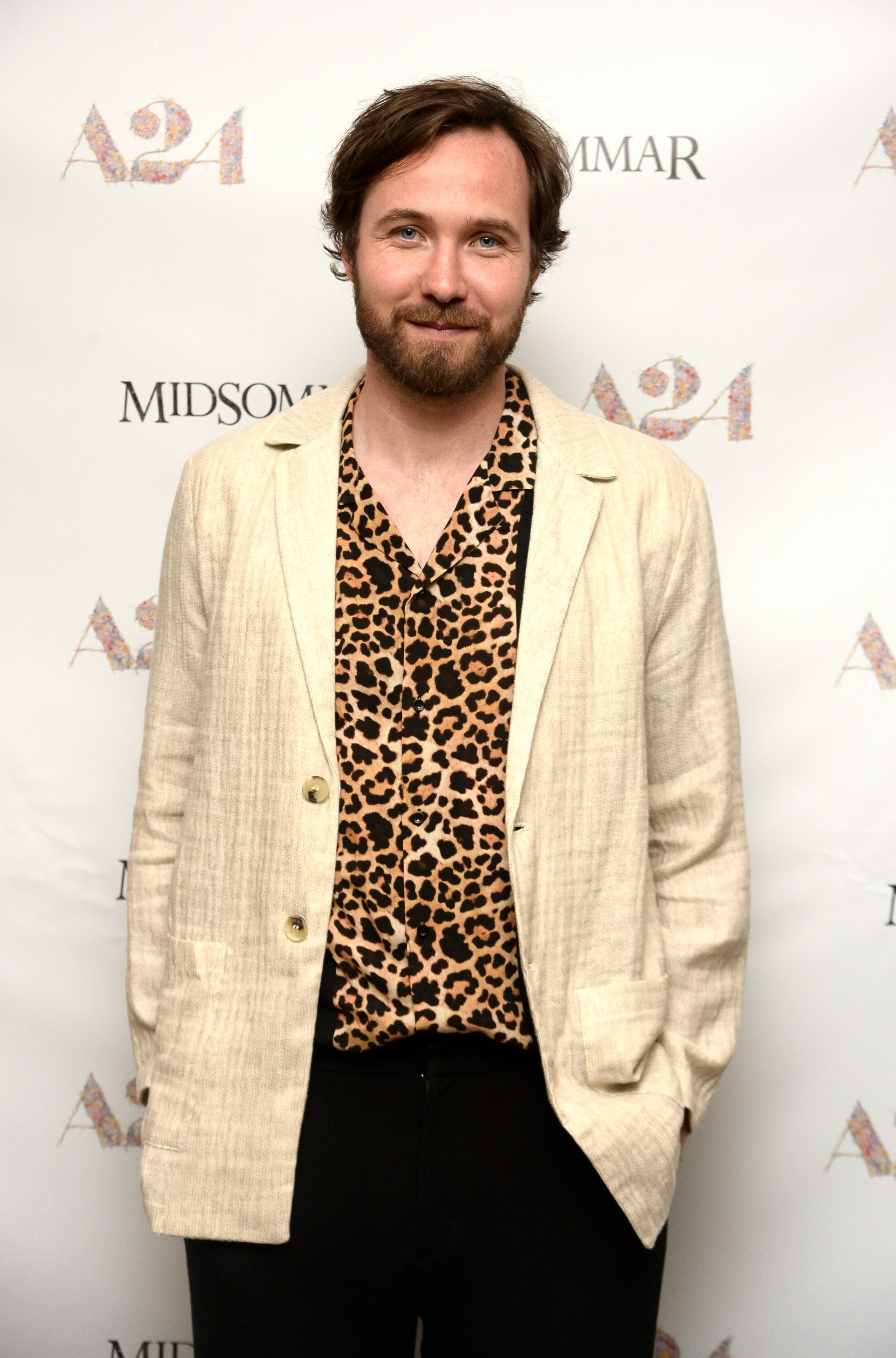 Vilhelm Blomgren in leopard-print button-down shirt and light-colored linen jacket and dark pants standing at a step-and-repeat for a viewing of A24's Midsommar, lightly smiling at camera
