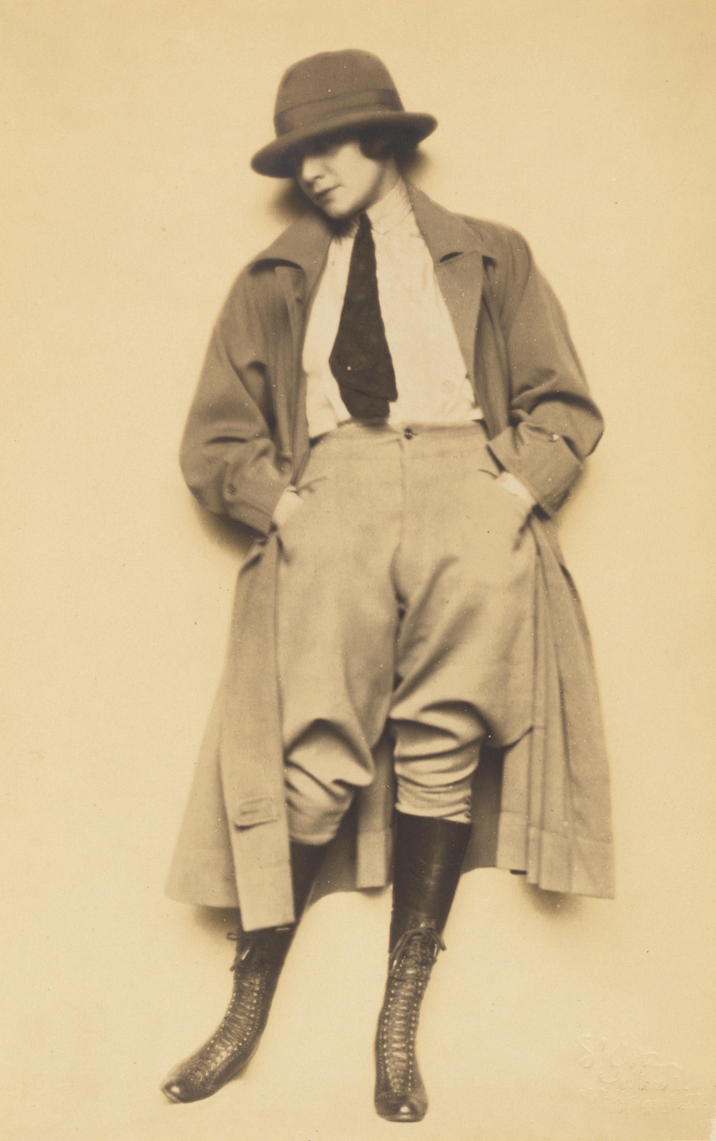 A woman dressed in man's clothing and a trench coat, facing the camera