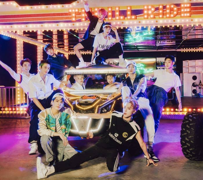 The members of the Boyz stand around a car in a bright arcade