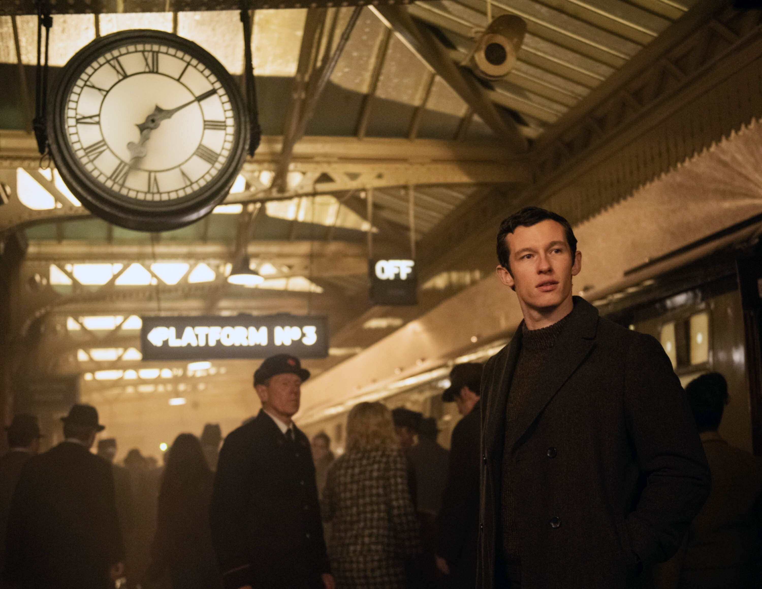 Anthony in a busy train station looking nervous, a large clock with Roman numerals above him to the left