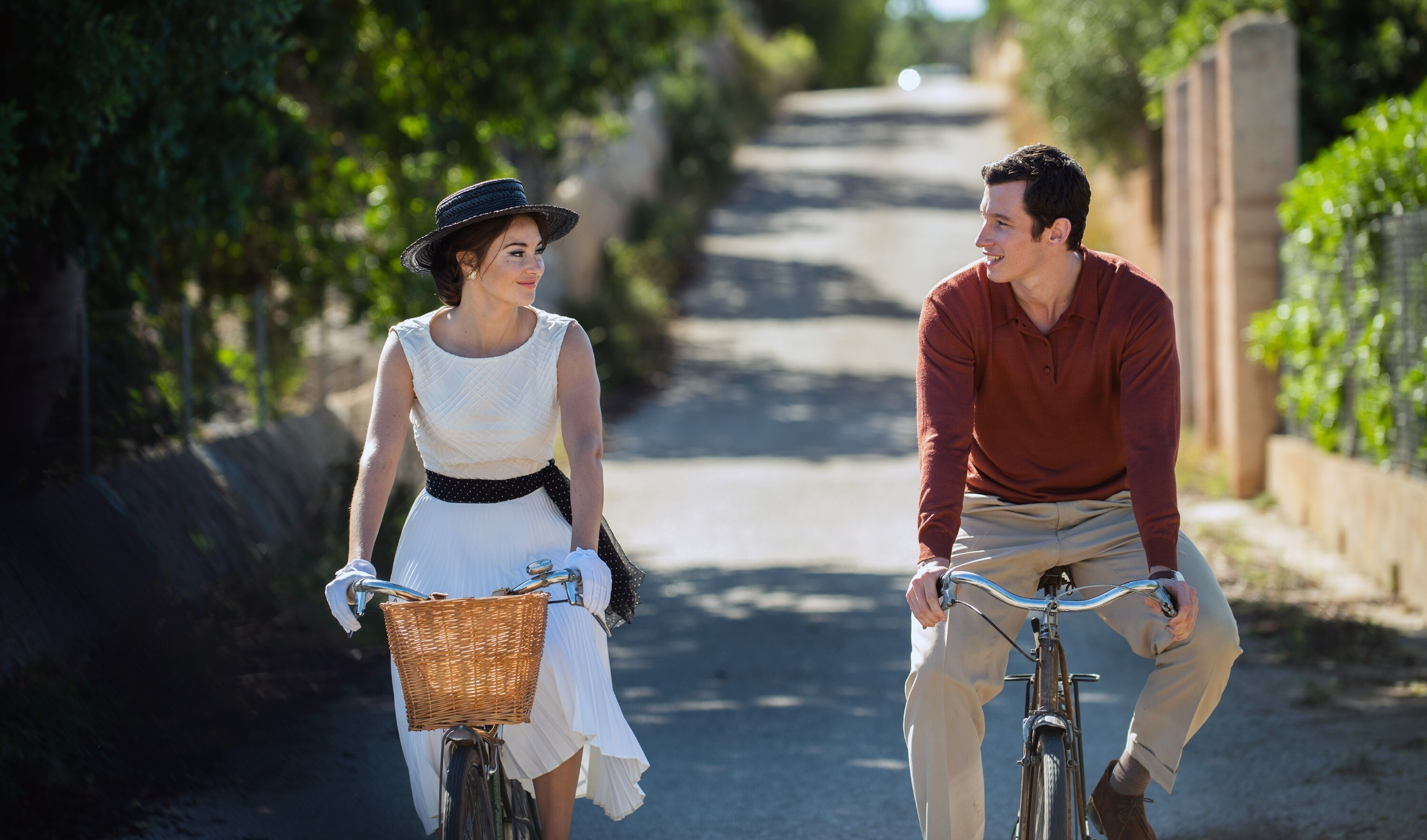 A woman on a bike with a hat and a man on a bike — they are looking at each other