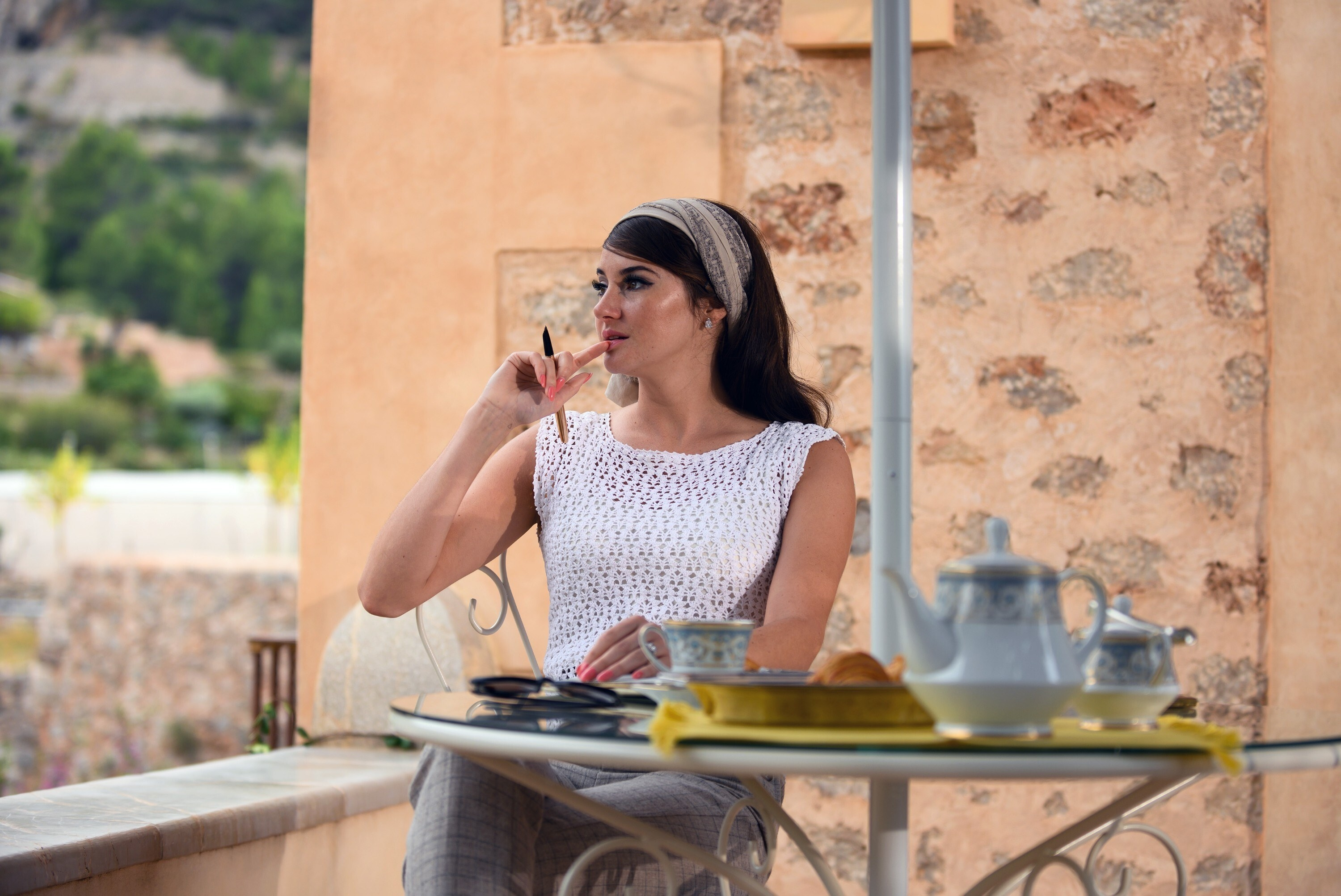 Jennifer at an outdoor table with tea, holding a pen and touching her mouth lost in thought