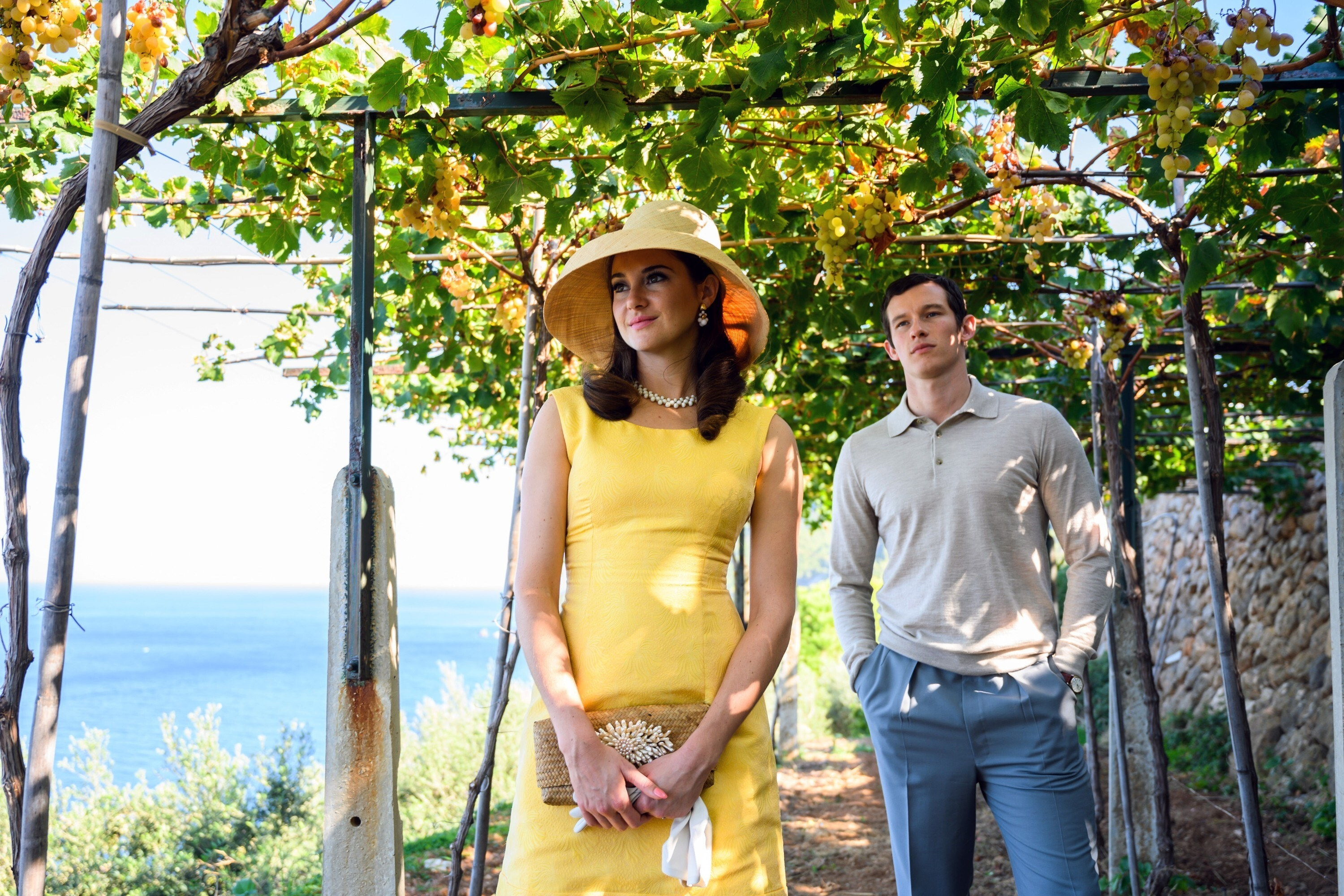 Jennifer in a tailored dress and hat, holding bag and gloves, with Anthony behind her in shirt with long sleeves and collar, and slacks, standing on a walkway under a canopy of leaves, ocean in the background