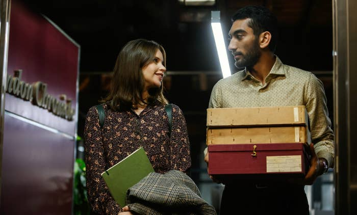 Ellie holding a notebook and her coat next to Rory holding archive boxes, standing in a doorway looking curiously at each other