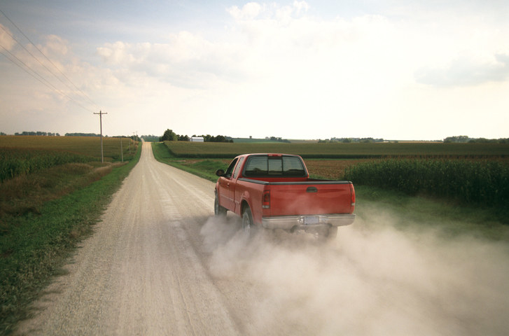 Red pick up truck traveling down dusty rural road