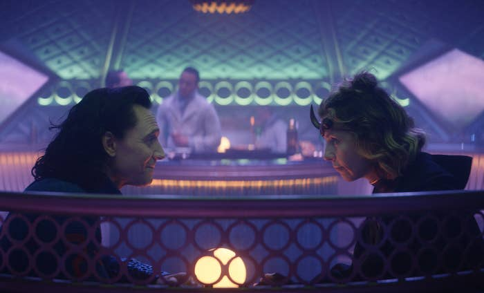 Loki sits with Sylvie in a futuristic restaurant with purple lighting