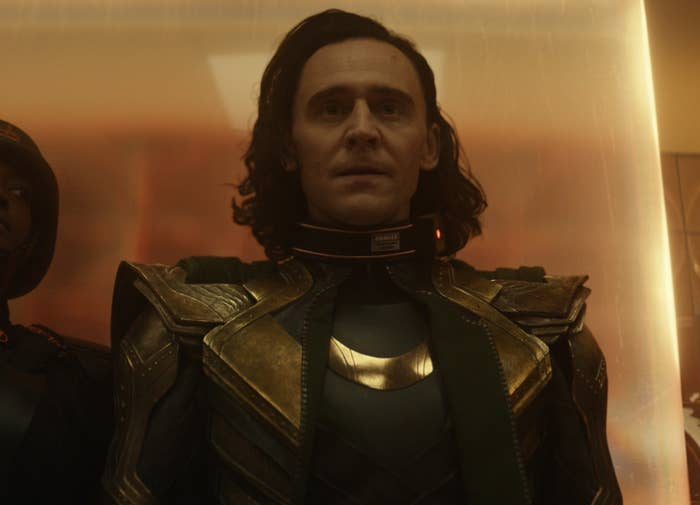 Loki enters a room in his amour looking slightly confused