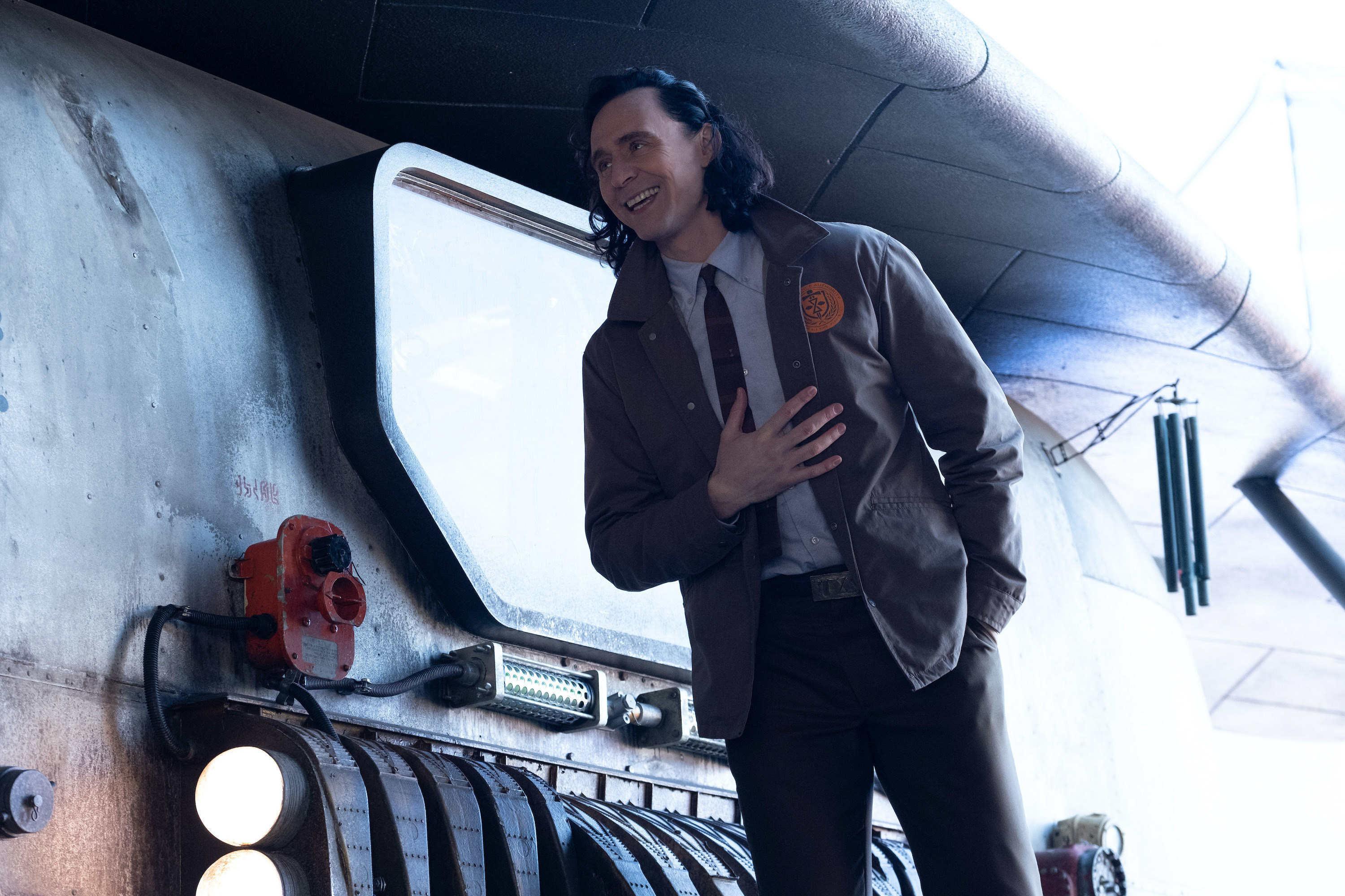Loki leans forward with his hand on his chest and smiles