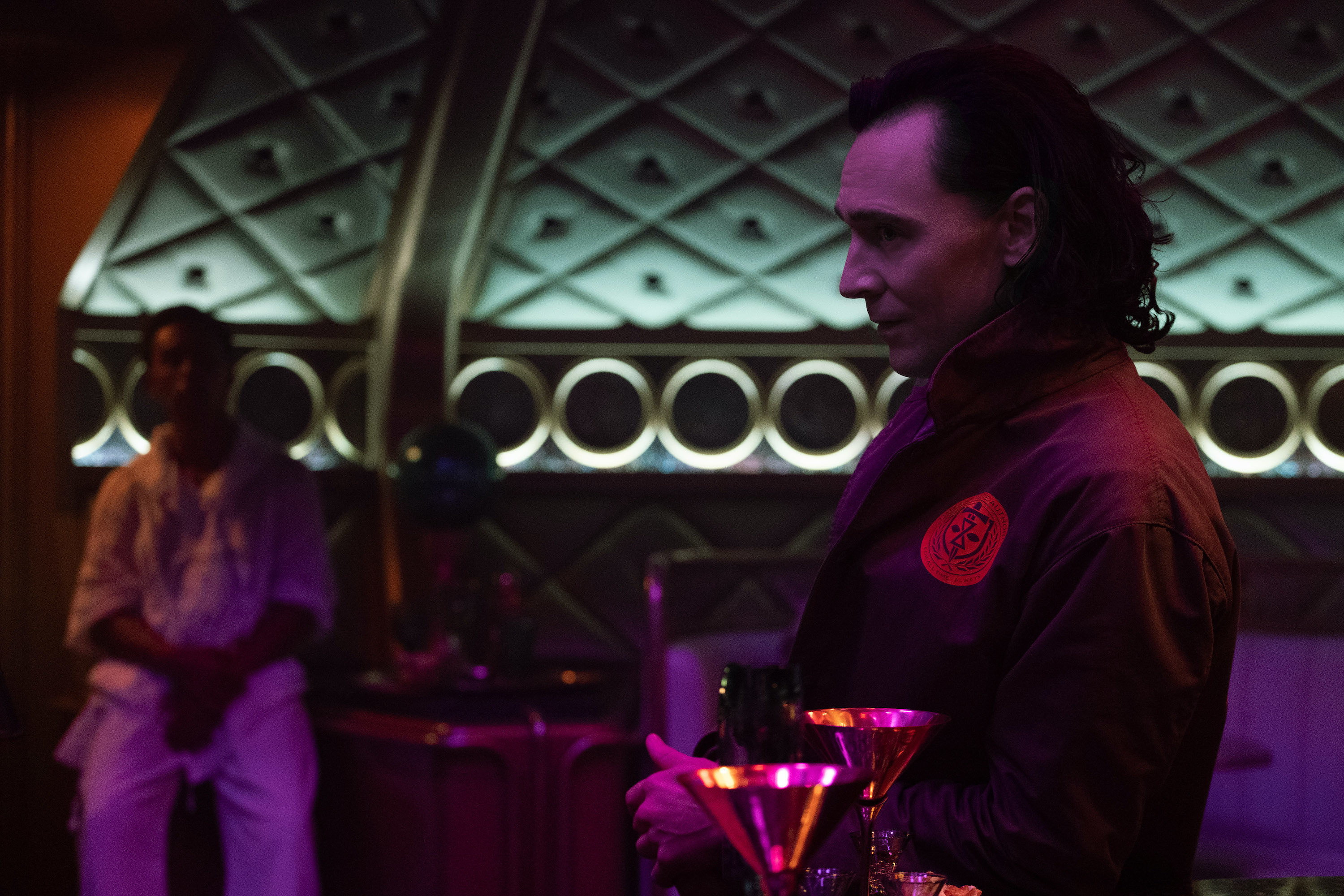 Loki sits at the bar at the restaurant and looks into the distance