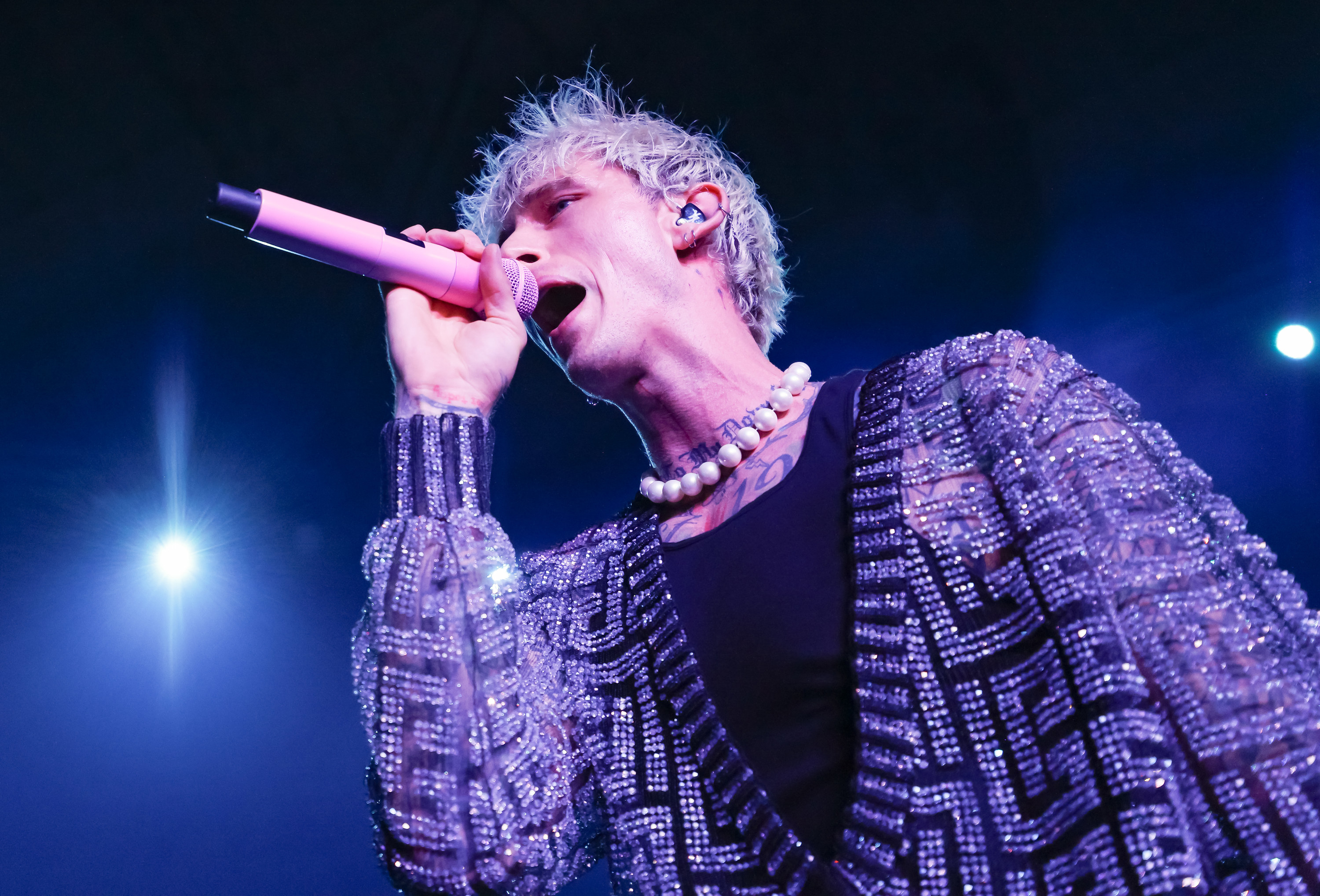 Machine Gun Kelly is photographed singing into a microphone onstage