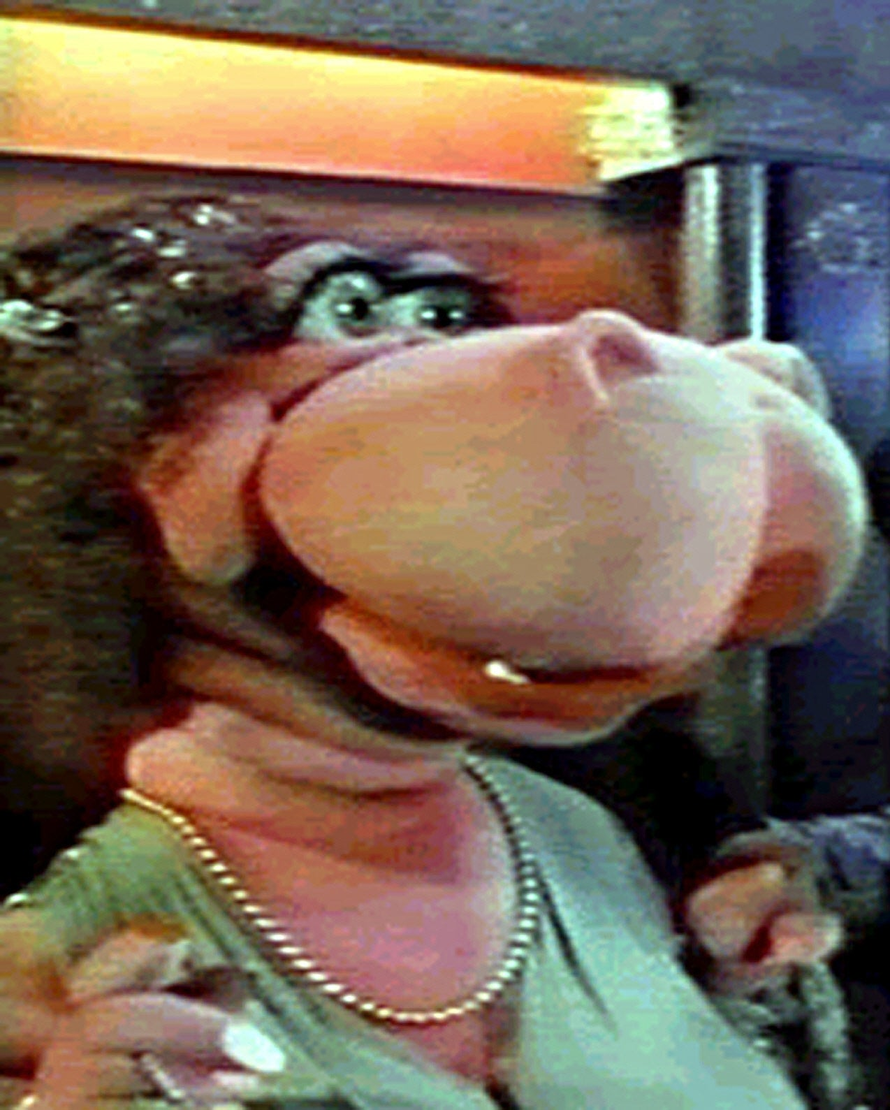 puppet with dress and pearl necklace and large snout but flesh-colored skin