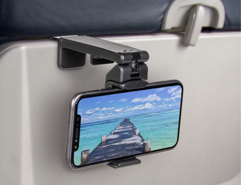 A phone mounted to the back of an airplane tray table