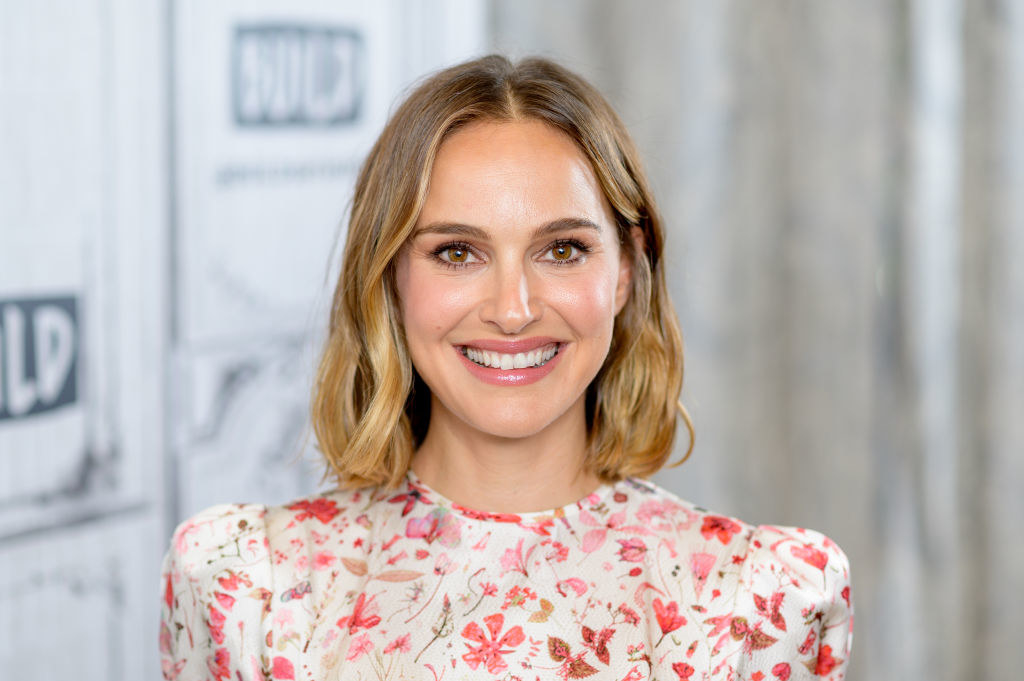Natalie smiling at the camera, wearing a floral outfit