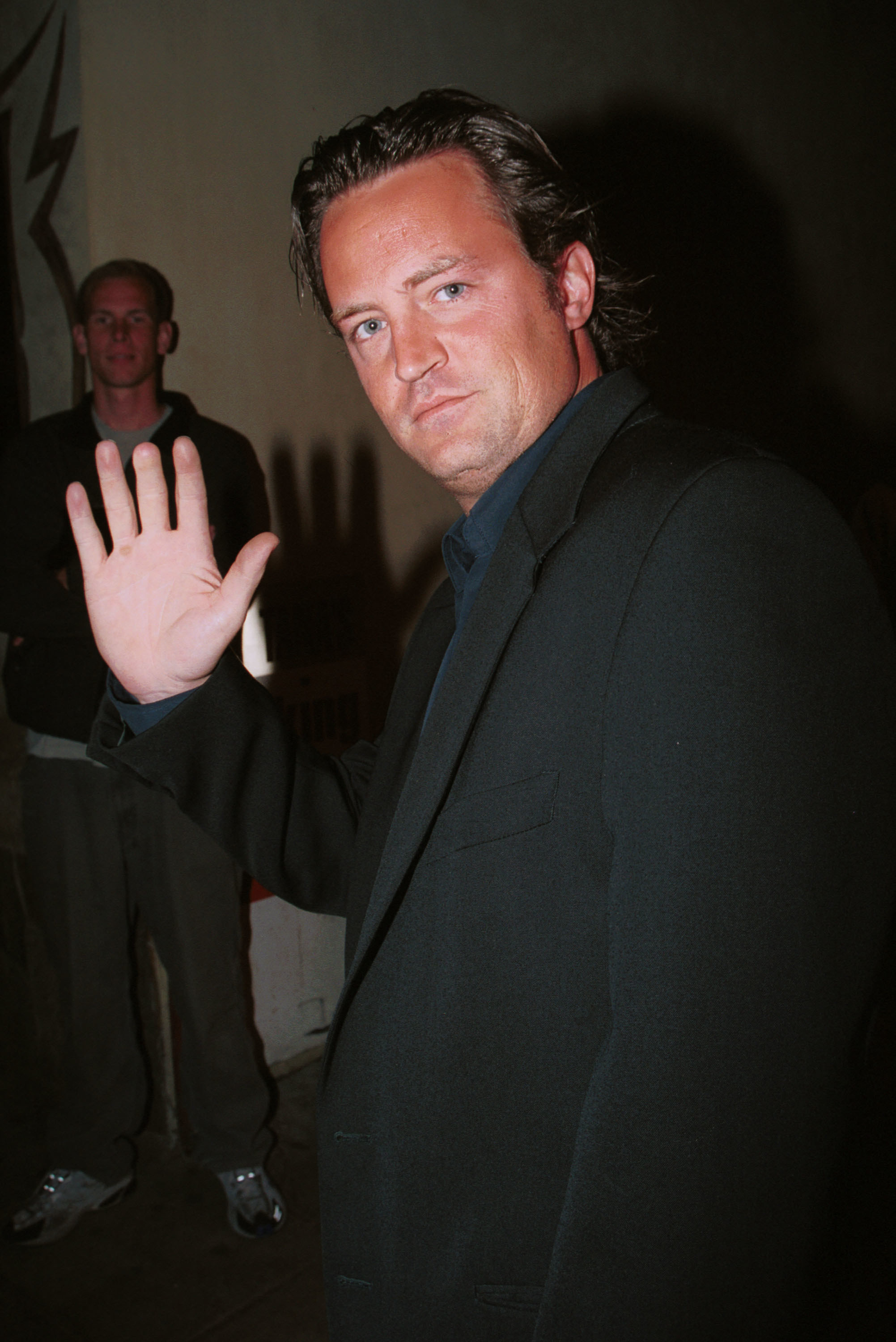 Matthew Perry showing off his short middle finger