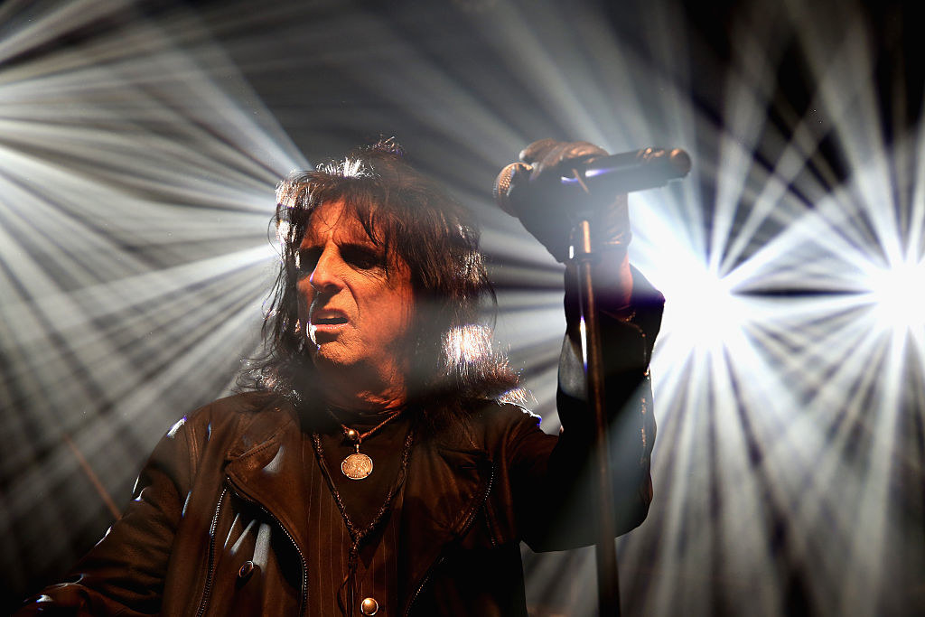Alice Cooper onstage with bright lights behind him
