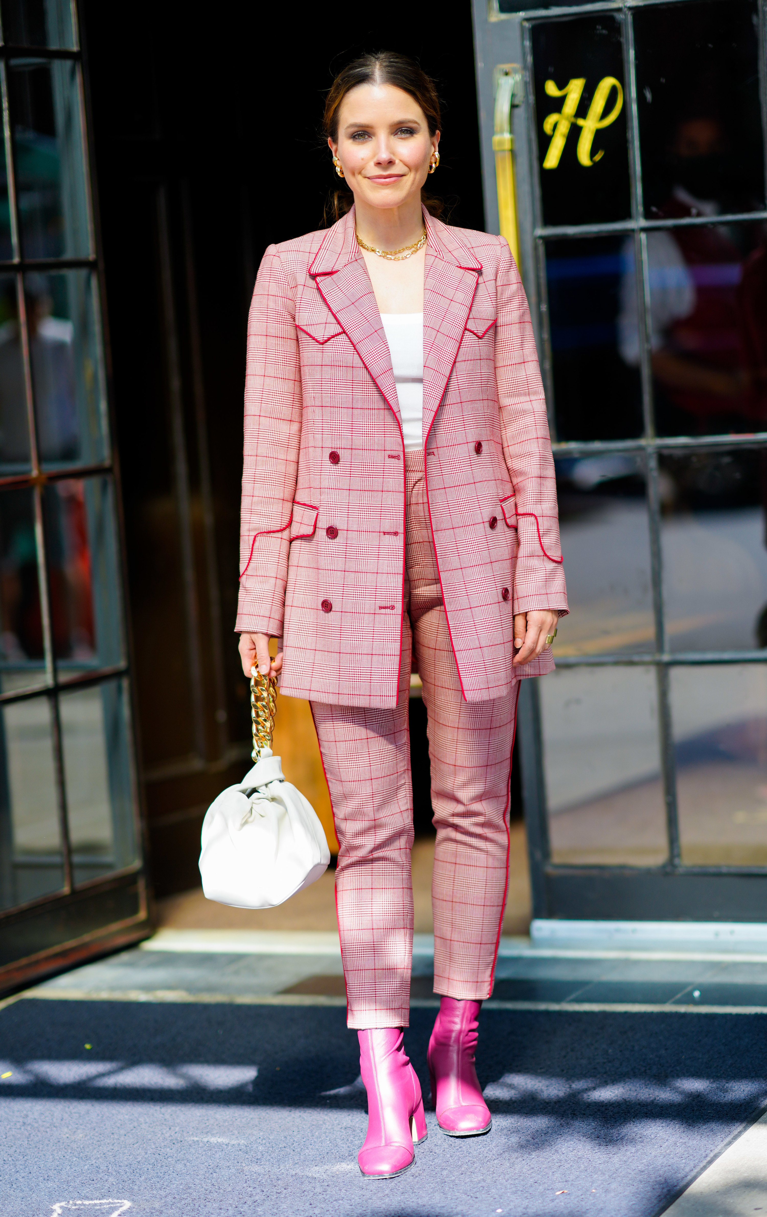 Sophia wears a pink plaid pantsuit with a gold chain necklace and bright pink boots.