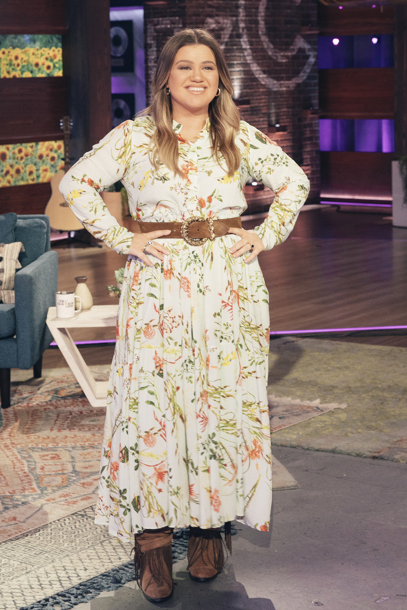 Kelly wears an ankle length floral patterned dress with a belt around her waist and fringe-covered booties.