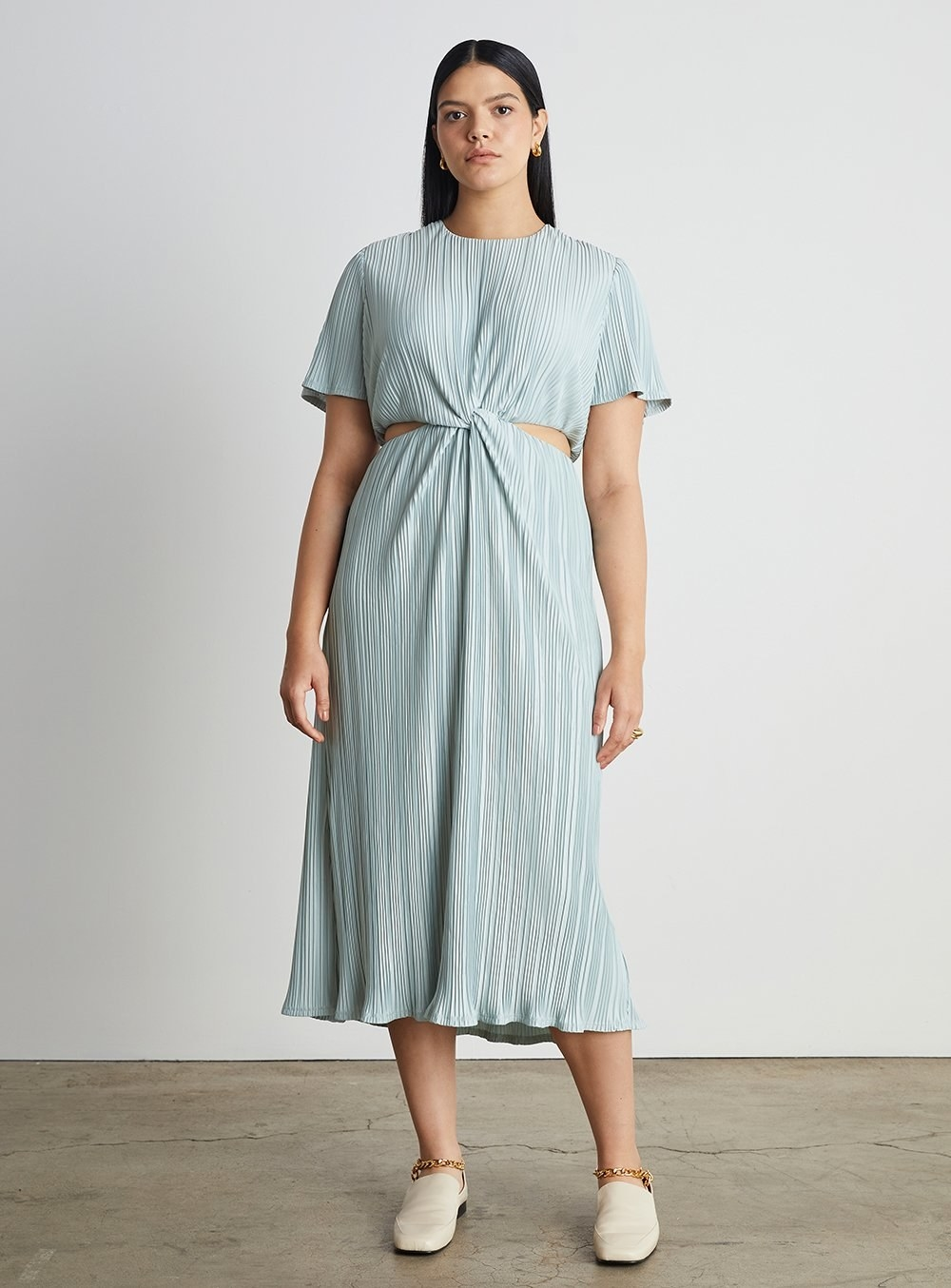 model wearing the midi pleated dress with short-sleeves and cut out sides and back in a light blue