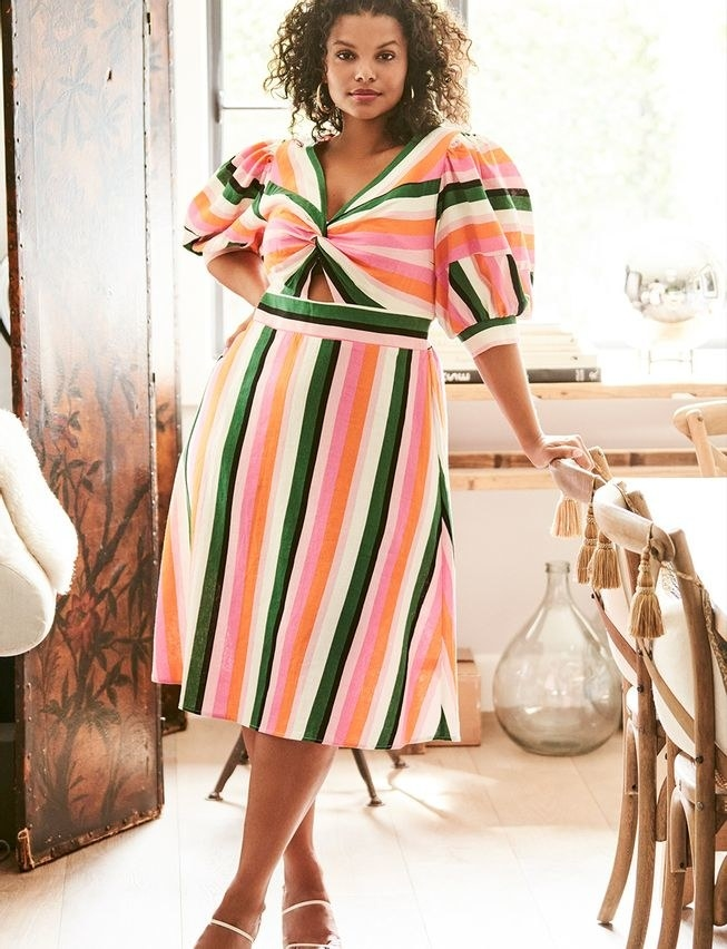 model wearing the knee-length puff-sleeve dress with green, white, orange, and pink stripes all over it